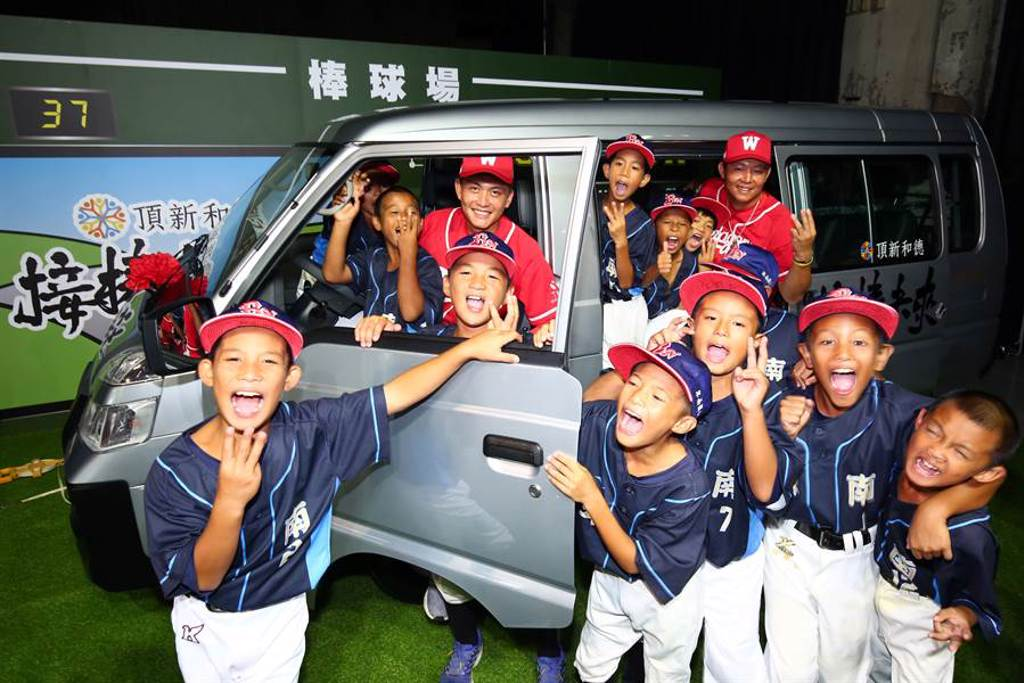 卑南國小少棒隊與味全龍隊選手劉基鴻(左)、黃柏豪(右)合影。(頂新和德文教基金會提供)