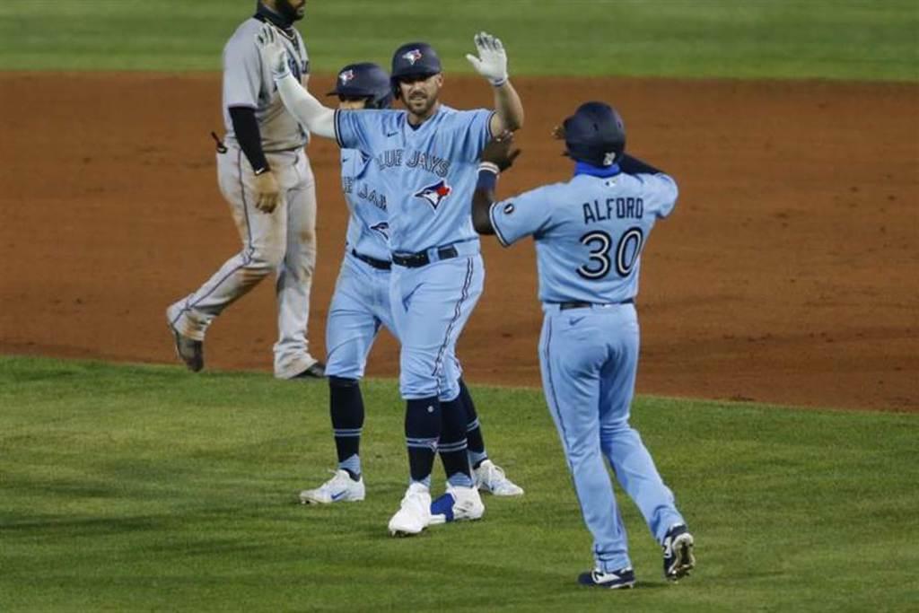 藍鳥隊在10局下由崔維斯蕭(右2)揮出再見安打,以5比4氣走馬林魚隊。(美聯社)