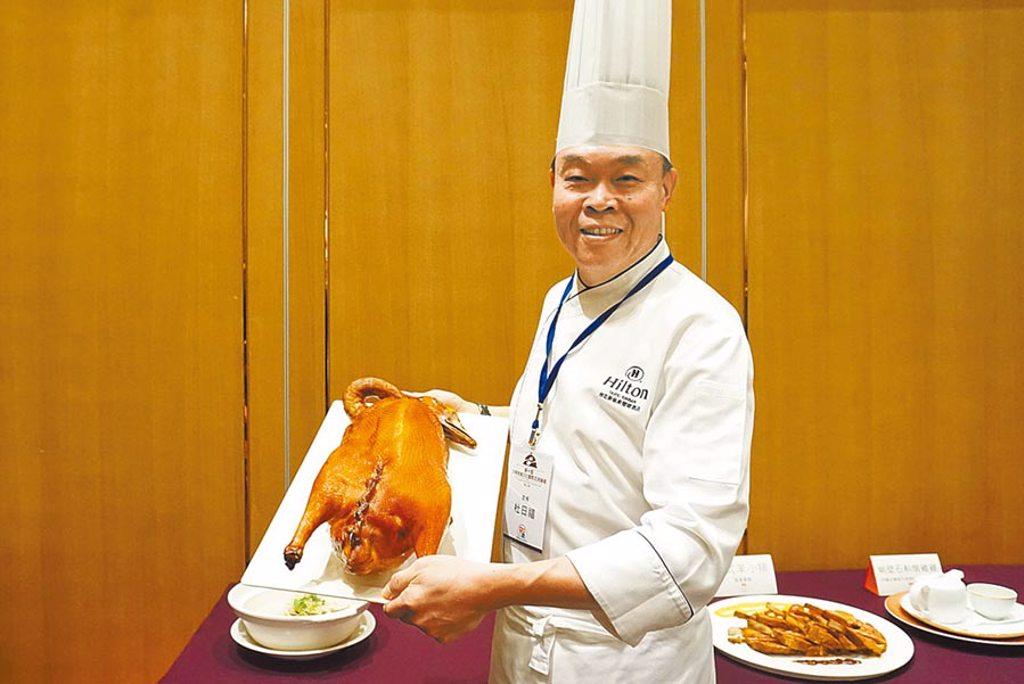 台北新板希爾頓行政主廚杜日福,端著「清雅嫣紅鵝」上菜,是該酒店的明星料理。(中華海峽兩岸餐飲連鎖經營協會提供)