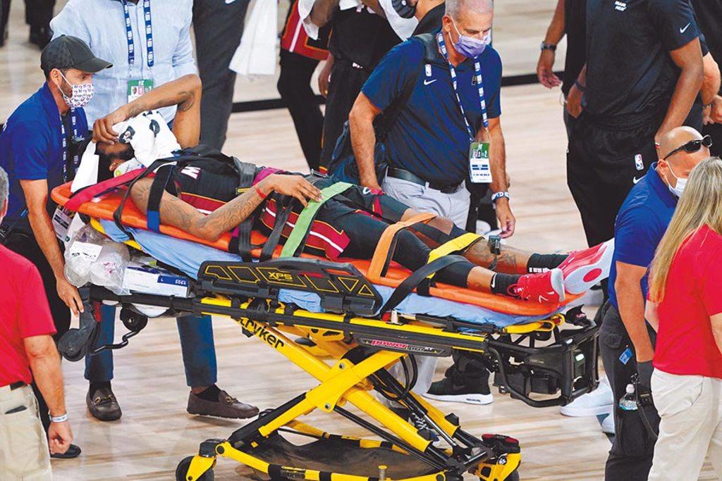 熱火德瑞克瓊斯因為頸椎扭傷被擔架抬出場外。(美聯社)