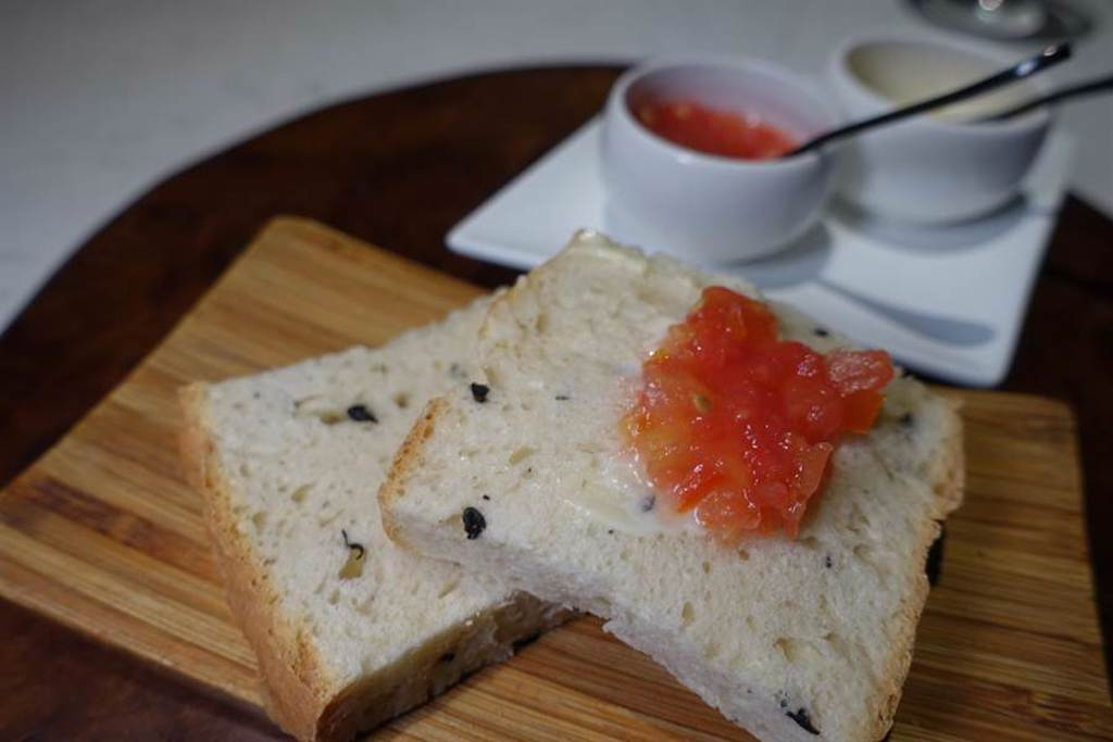 「西班牙鄉村手擀農夫麵包」帶迷迭香及黑橄欖的香氣,佐新鮮牛番茄及蒜味美乃滋。(黃采薇攝)