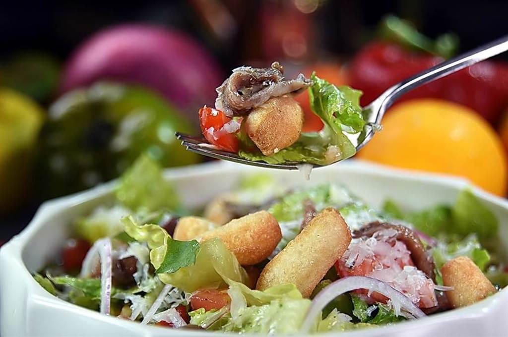 在〈義舍廚房〉,炸披薩麵糰可用來取代麵包丁,作為〈鯷魚蘿蔓沙拉〉裡的配料,豐富口感層次並增加飽足感。(圖/姚舜)