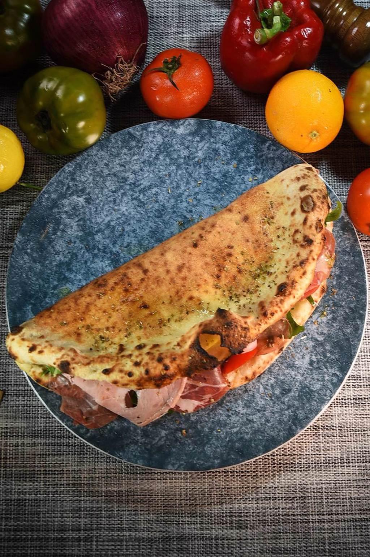 呈「半月形」的〈火腿起司微笑披薩〉,也是拿坡里人發明的披薩。(圖/姚舜)