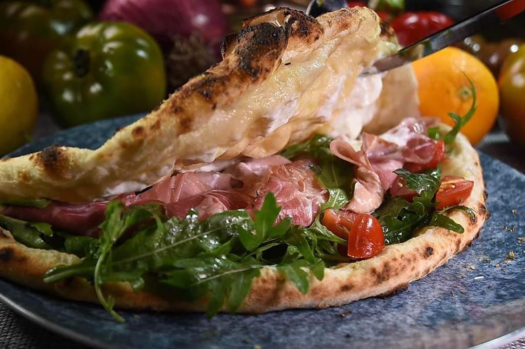〈火腿起司微笑披薩〉有點像「袋餅」,裡面的內餡有芝麻葉、小番茄、起司,和義式Coppa臘肉與Mortadella肉腸。(圖/姚舜)