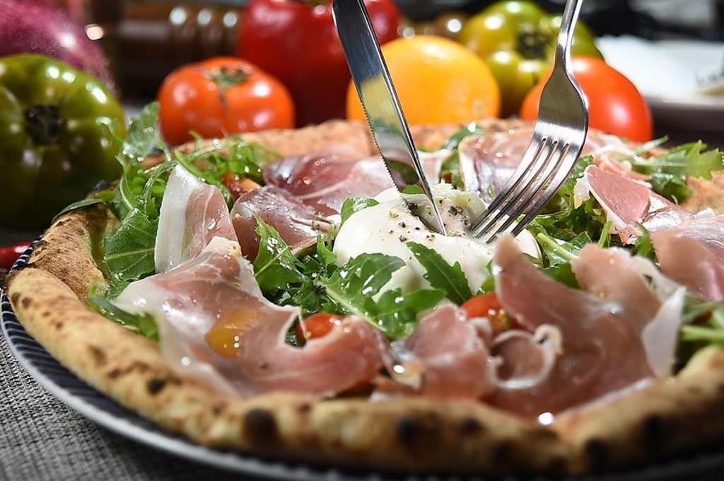 享用〈義舍招牌披薩〉時,可先用刀子將整球的布拉塔起司畫開,再與配料拌在一起後,再將披薩切片吃食。(圖/姚舜)