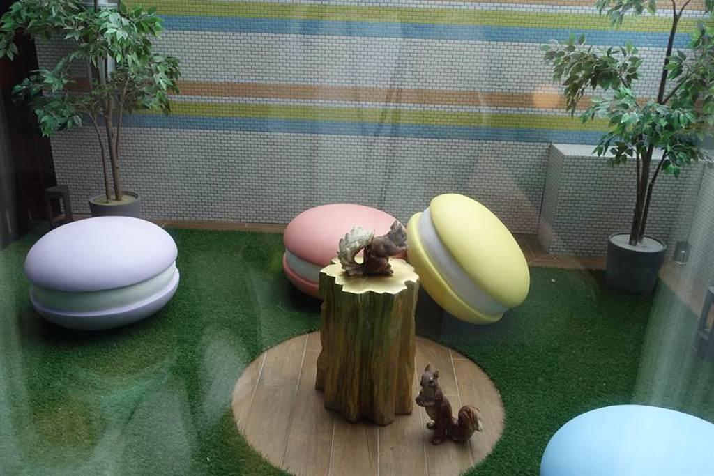主題客房之一的「好饗甜甜Sweets」兩大床面向造景—松鼠吃橡實、四周有繽紛馬卡龍,為可欣賞的景觀、禁止將玻璃門打開。(黃采薇攝)