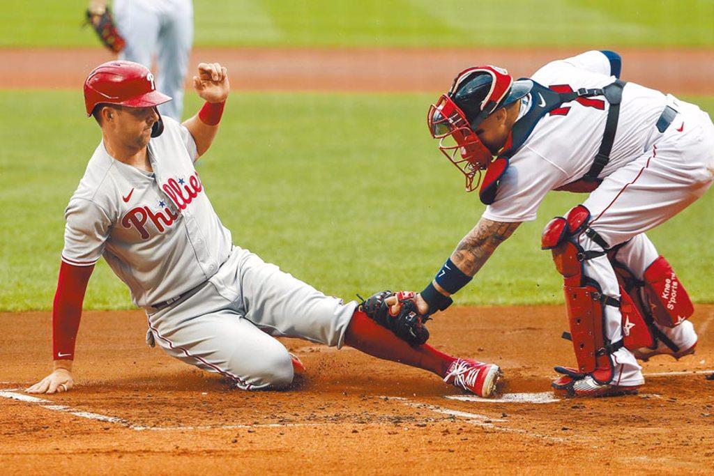 費城人霍斯金斯(左)滑回本壘得分,紅襪捕手瓦茲奎茲觸殺慢了一步。(美聯社)