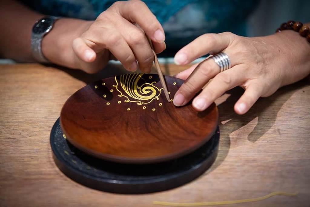 楊琇文將「漆線雕」應用在生漆塗製的木盤上,進行複合媒材創作。(袁庭堯攝)