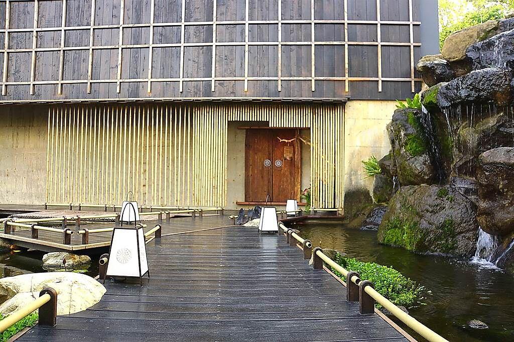 走進台中新餐廳〈飛花落院〉主建建築,必須走過瀑布與水池相佐的木橋棧道,心境亦隨之轉換。(圖/姚舜)