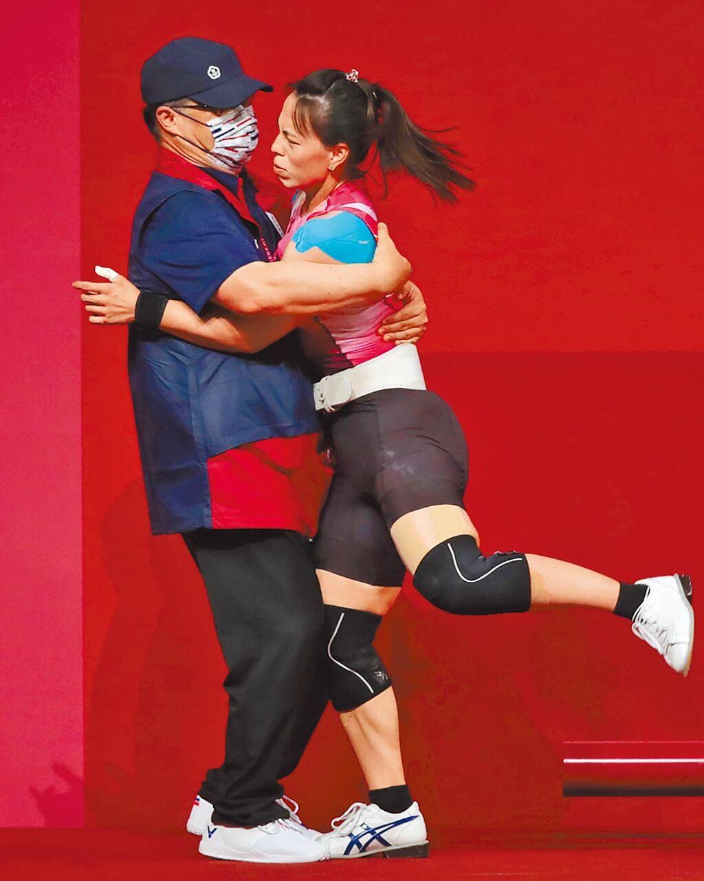 東京奧運女子舉重59公斤級由中華隊的郭婞淳(右)拿到金牌,賽後她與教練擁抱。(季志翔攝)
